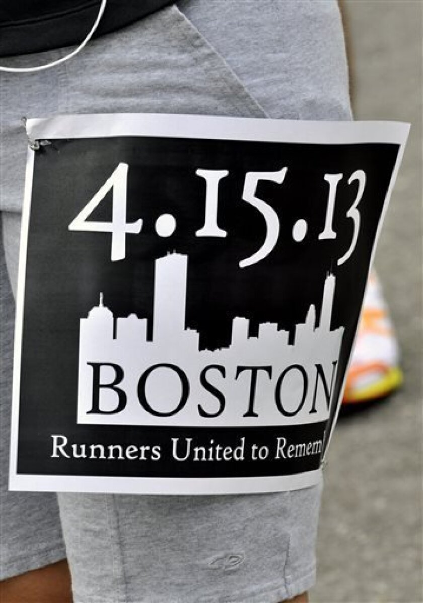 A member of the Wilmington Roadrunners, a group that meets weekly to run in downtown Wilmington, N.C.,wears a special pennant on Tuesday, April 16, 2013 to show their respect for the victims of the Monday bombings at the Boston Marathon. Prior to their run they held hands in a prayer. (AP Photo/The