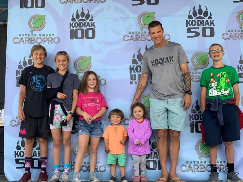 Ben Brown at the finish line of the 100-mile Kodiak Ultra with his children.