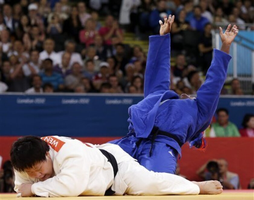 Cuba's Idalys Ortiz China's Wen Tong compete and during the women's over 78-kg judo competition at the 2012 Summer Olympics, Friday, Aug. 3, 2012, in London. (AP Photo/Paul Sancya)
