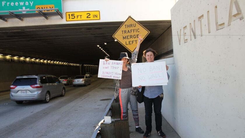 Artists Rachel Mason, left, and Ilona Berger make their way to the protest at LAX.