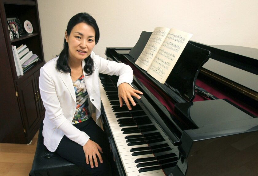Portrait of Cho Hyun Park with her piano at home.