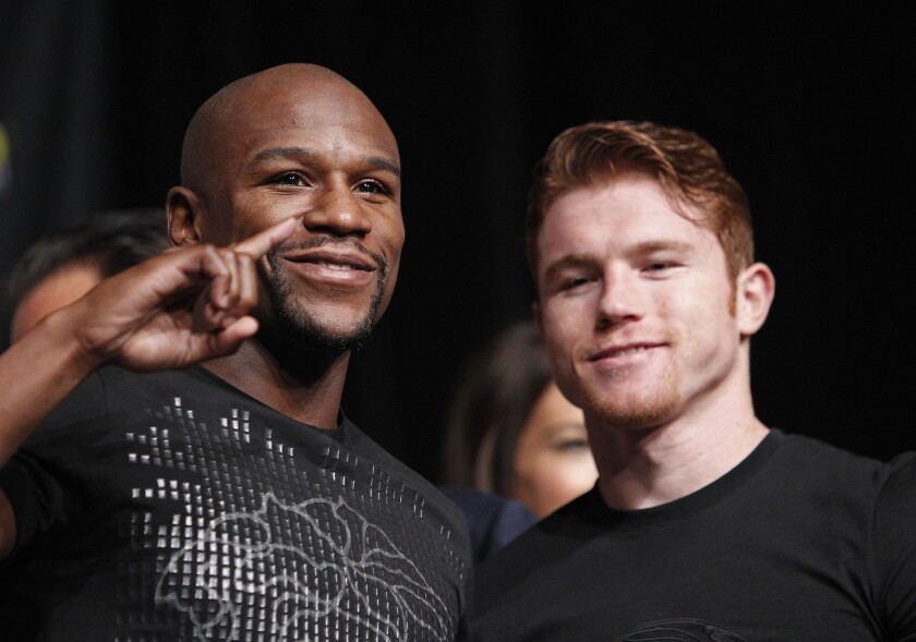 """Floyd Mayweather Jr., left, and Saul """"Canelo"""" Alvarez pose during a news conference Wednesday in Las Vegas to promote their fight on Saturday."""