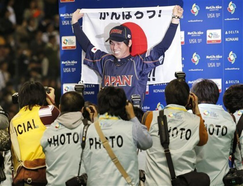 Japan's starter Kenta Maeda poses with a Japanese flag for photographers after beating the Netherlands in their World Baseball Classic second round game at Tokyo Dome in Tokyo, Sunday, March 10, 2013. The game was called in the bottom of the seventh inning with a score of 16-4. (AP Photo/Koji Sasah