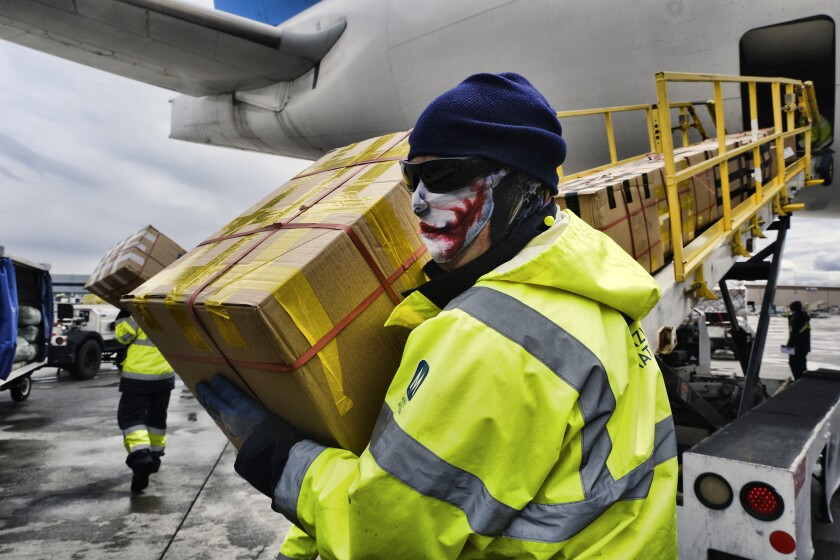 Crews at Los Angeles International Airport unload supplies of personal protective equipment.