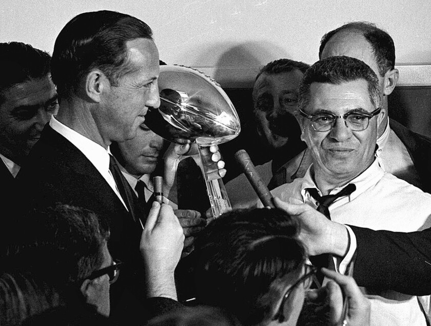 NFL Commissioner Pete Rozelle, left, presents the championship trophy to Green Bay Packers coach Vince Lombardi after they beat the Kansas City Chiefs in the first Super Bowl in Los Angeles.