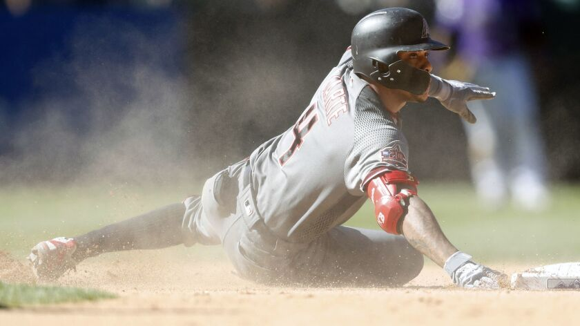 Arizona Diamondbacks' Ketel Marte slides safely into second base with an RBI-double off Colorado Rockies relief pitcher Yency Almonte in the seventh inning of a baseball game Thursday, Sept. 13, 2018, in Denver. (AP Photo/David Zalubowski)