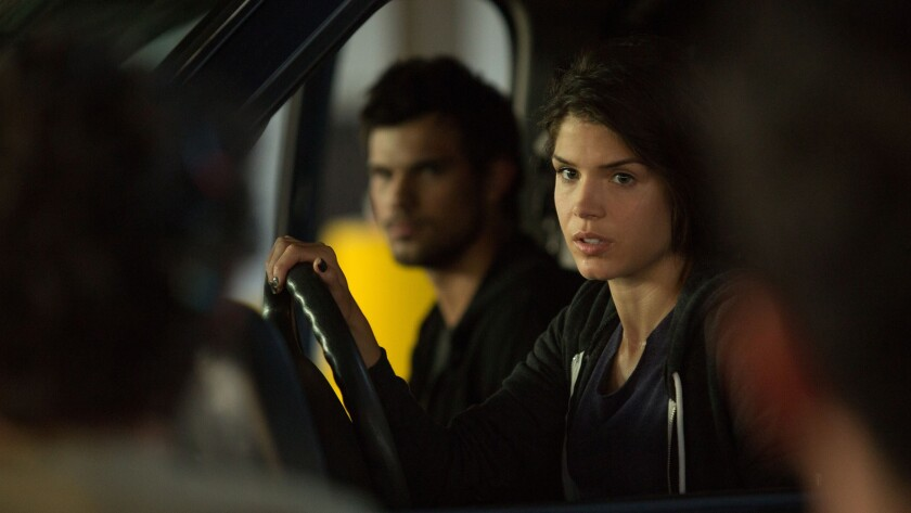 "Nikki (Marie Avgeropoulos), right, and Cam (Taylor Lautner) in the movie, ""Tracers."""