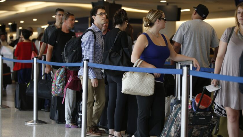 Travelers wait at the Delta Air Lines counter at Los Angeles International Airport on Sept. 4, 2015, the getaway day for the Labor Day holiday. Industry leaders predict 16.5 million people will travel on U.S. carriers this holiday weekend.