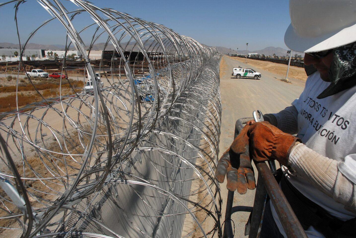 """Fotografía en la que se observa a un trabajador de una empresa subcontratada por la Patrulla fronteriza de Estados Unidos del sector San Diego al instalar alambre de cuchillas o """"razor wire"""" en la valla que separa San Diego (EEUU) de Tijuana (México), y que desde comienzos del mes en curso está siendo reforzada con este material. Según la Patrulla Fronteriza, un promedio de tres agentes son atacados diariamente a lo largo de la frontera, sobre todo en los sectores de California y Arizona. EFE/DAVID MAUNG"""