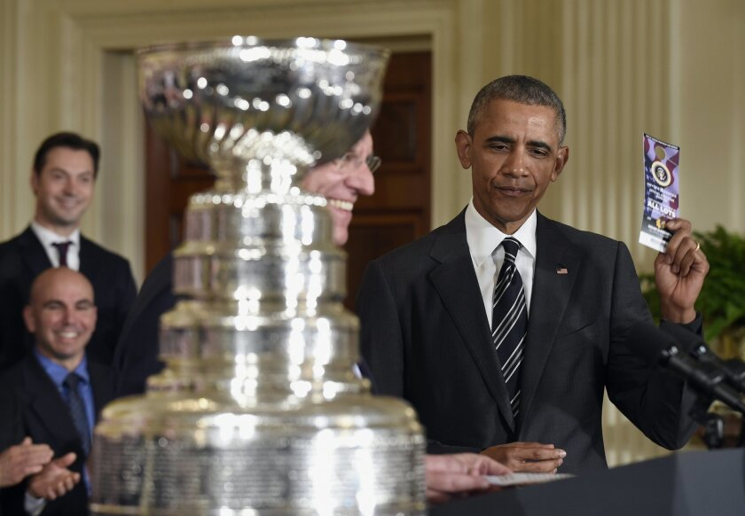 President Barack Obama holds up a hangtag parking pass that he was given to him by Chicago Blackhawks hockey team Chairman Rocky Wirtz, left, Thursday, Feb. 18, 2016, during a ceremony to honor the 2015 NHL Stanley Cup Champion Chicago Blackhawks in the East Room of the White House in Washington.