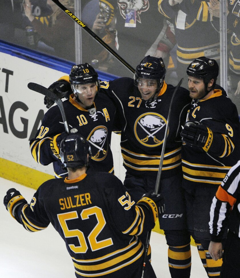 Buffalo Sabres' Alexander Sulzer (52) celebrates with teammates Christian Ehrhoff (10), Matt D'Agostini (27) and Steve Ott (9) after D'Agostini scored the game-winning goal in the overtime session against the  Boston Bruins during an NHL hockey game in Buffalo, N.Y., Wednesday, Feb. 26,  2014. Buff