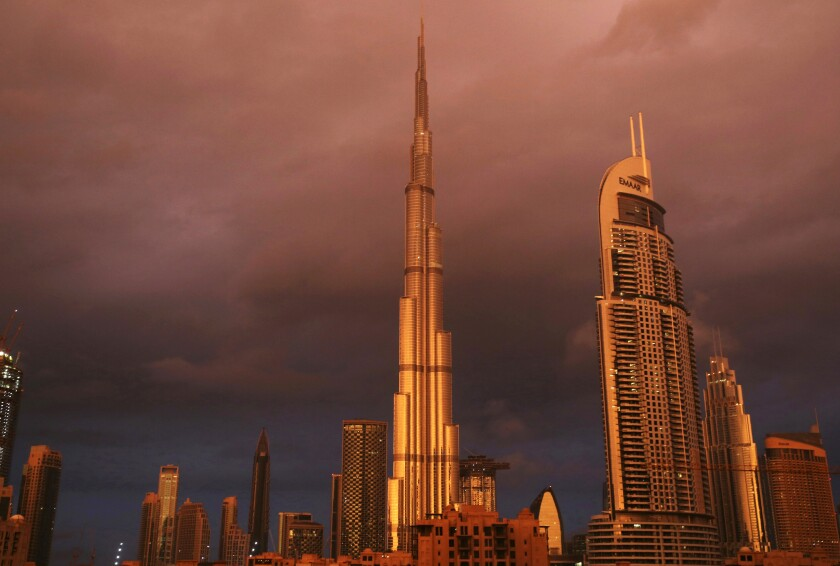 FILE - In this Monday, Nov. 26, 2018 file photo, sunlight reflects off the Burj Khalifa, the world's tallest building, during a rain shower in Dubai, United Arab Emirates. The Dubai-based construction company that helped build the world's tallest building and other engineering marvels in the United Arab Emirates announced Thursday, Oct. 1, 2020, it would enter liquidation, the final step in a long collapse from the country's economic crisis a decade ago hastened by the coronavirus pandemic. (AP Photo/Jon Gambrell, File)