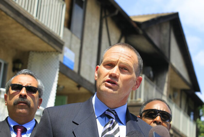 United Firefighter of Los Angeles City leader Frank Lima, center, speaks during a news conference outside a heavily damaged apartment building on Riverton Avenue in North Hollywood last spring.