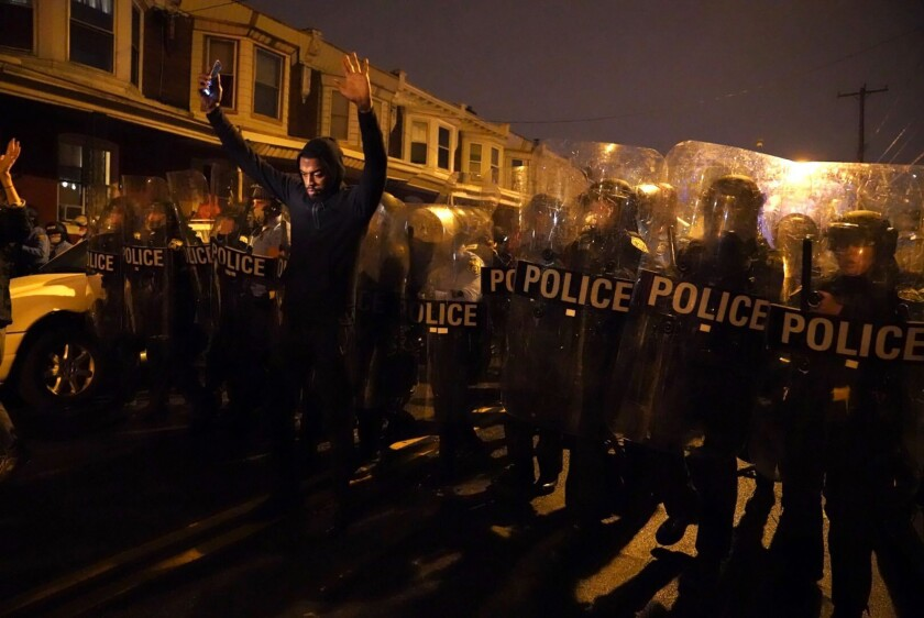 A demonstrator lifts his hands before police during a protest of a fatal police shooting in Philadelphia.