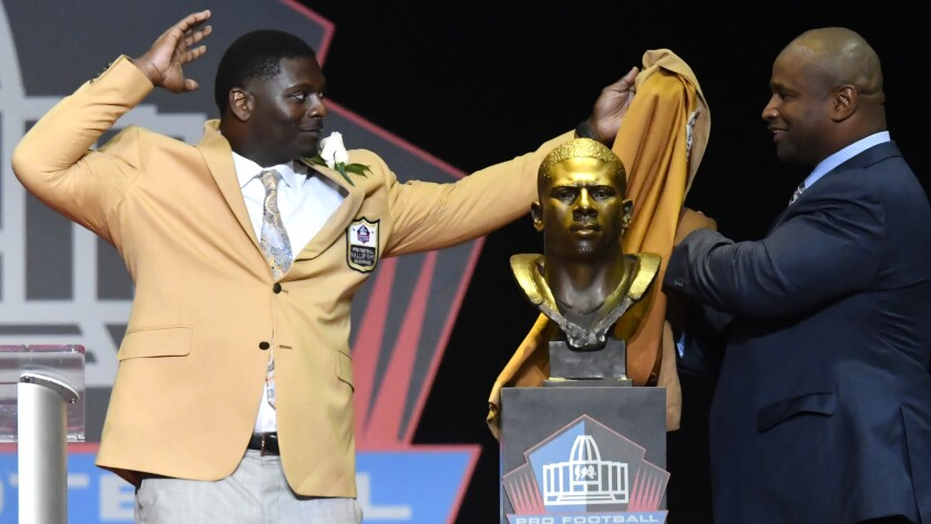 LaDainian Tomlinson, left, and his presenter, Lorenzo Neal, unveil his bust before his speech during the induction ceremony at the Pro Football Hall of Fame on Aug. 5.