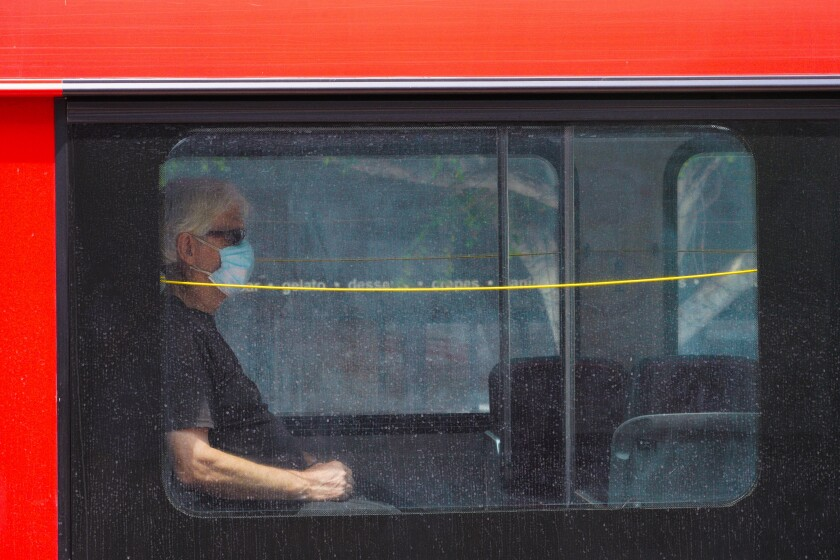 At Hillcrest a passenger onboard the MTS bus wears a face mask while riding down University Avenue.