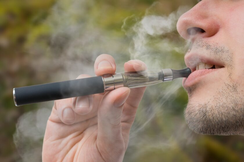 Young smoker is vaping e-cigarette or vaporizer.