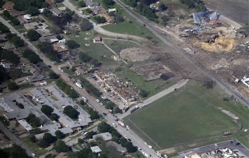 This Thursday, April 18, 2013 aerial photo shows the remains of a nursing home, left, apartment complex, center, and fertilizer plant, right, destroyed by an explosion in West, Texas. Rescuers searched the smoking remnants for survivors of Wednesday night's thunderous fertilizer plant explosion, gingerly checking smashed houses and apartments for anyone still trapped in debris while the community awaited word on the number of dead. Initial reports put the fatalities as high as 15, but later in t