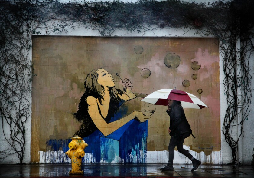 A pedestrian walks in the rain past a mural on South Hewitt Street in the Arts District of Los Angeles in February.