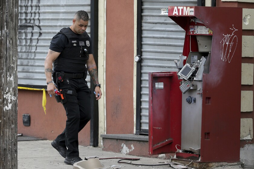 A member of the Philadelphia bomb squad surveys the scene after an ATM machine was blown-up at 2207 N. 2nd Street in Philadelphia, Tuesday, June 2, 2020. (David Maialetti/The Philadelphia Inquirer via AP)