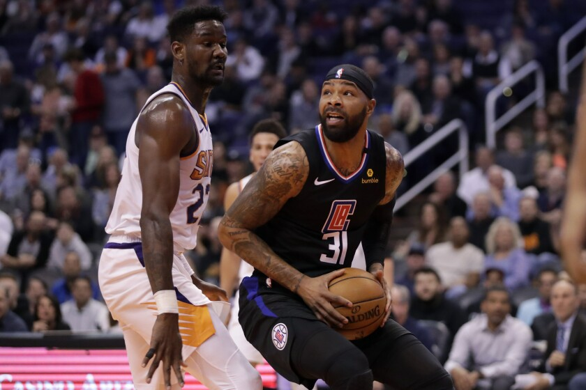 Clippers forward Marcus Morris spins to the basket to try to score against Suns center Deandre Ayton during the first half of a game Feb. 26, 2020, in Phoenix.