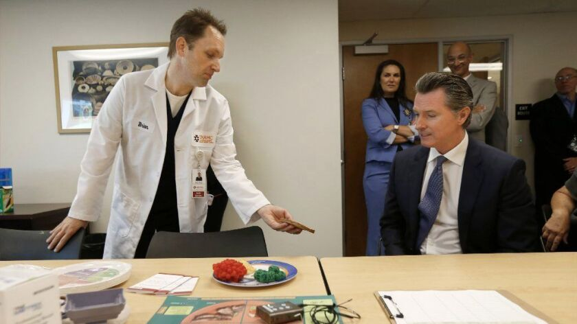 Gov. Gavin Newsom, right, meets with diabetes program coordinator Brian Shaw during a July 9 visit to the Sacramento Native American Health Center.