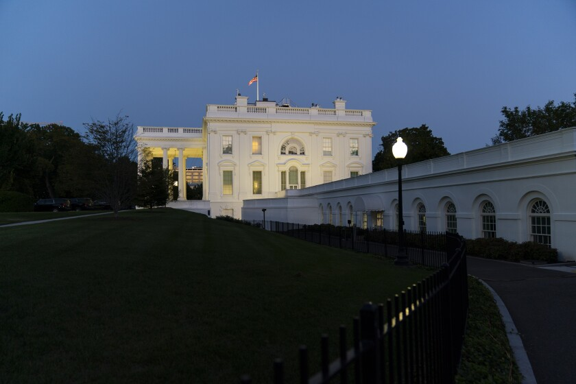President Donald Trump stands on the balcony outside of the Blue Room as returns to the White House