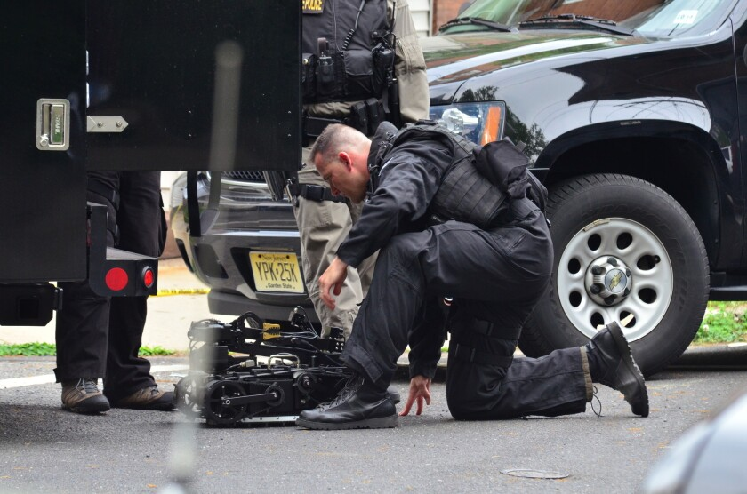 A state police SWAT team member readies a robot to enter a home where a man had barricaded himself in Trenton, N.J.