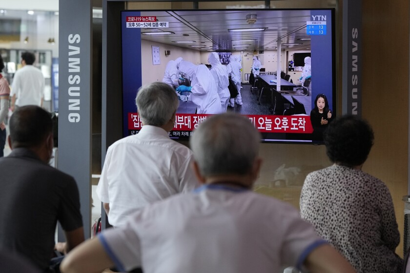 People watch a TV showing an image of South Korean service members wearing protective clothes