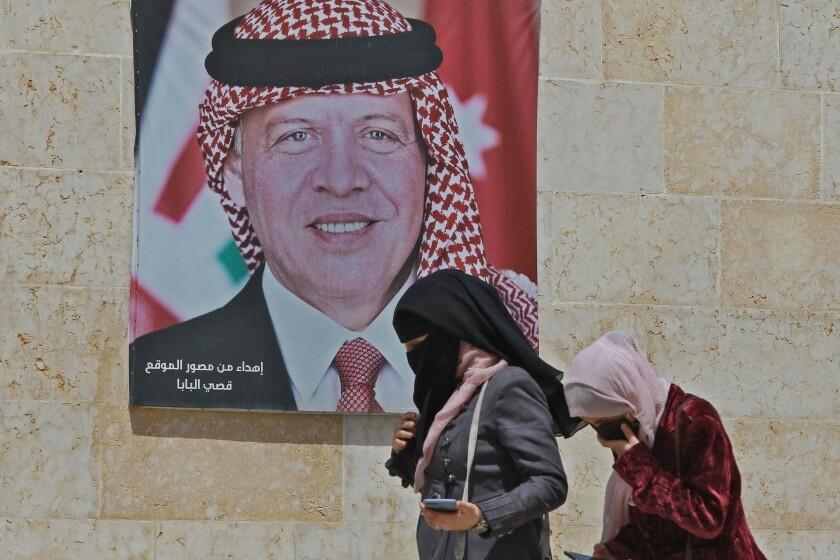 Women walk past a poster of Jordan's King Abdullah II on a street in the capital Amman.
