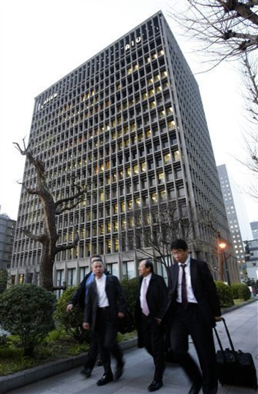 FILE - In this March 19, 2009, businessmen walk by the AIG building in Tokyo, Japan. Embattled insurer American International Group Inc. said Monday, May 11, 2009, it is selling its Japanese headquarters to Nippon Life Insurance Co. for $1.2 billion in cash. (AP Photo/Shizuo Kambayashi, file)