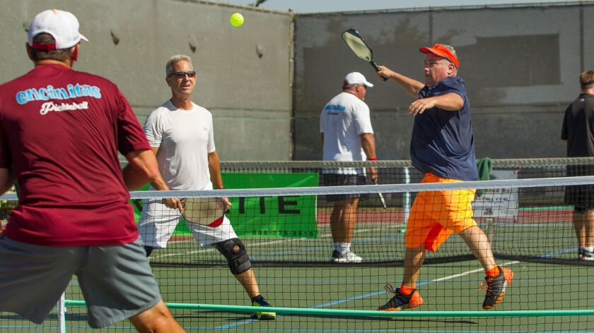 Craig Evans, right, and teammate Howard Fromberg compete in a doubles match during the Surf City Pickleball Tournament on Friday at Murdy Park in Huntington Beach.
