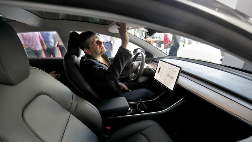 Jay Corson, of Sherman Oaks, who is on a waiting list to purchase the car, checks out the Tesla Mode