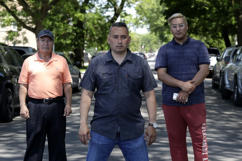Juan Rodriguez, left, Raul Montes Jr., center, and Radames Pina pose for a photo Tuesday, June 2, 2020, in Chicago. Activists and residents are angry that Little Village businesses and homes are being vandalized amid protests sparked by the death of George Floyd in police custody in Minneapolis, on May 25. (AP Photo/Nam Y. Huh)