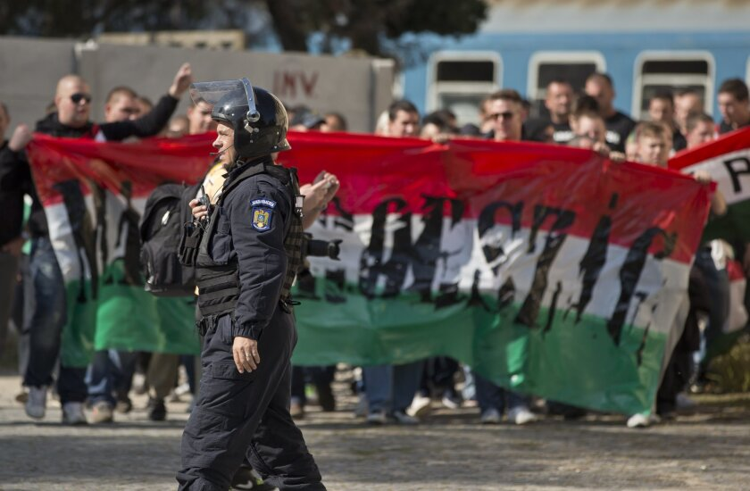 FILE - In this Saturday, Oct. 11, 2014 file photo, a Romanian riot policer officer walks backdropped by chanting Hungarian soccer fans at a railway station in Bucharest, Romania. Hooliganism is making a comeback, and the timing could be bad with four high-risk matches in the first week of the Europ