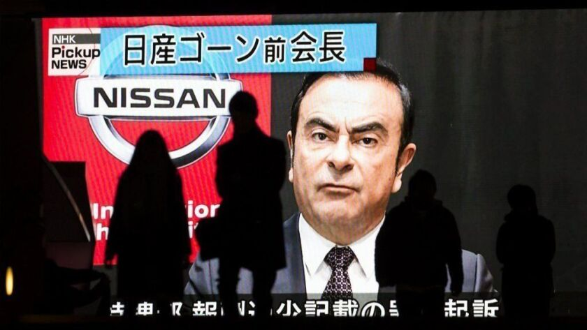 Pedestrians walk in front of a monitor showing an image of former Nissan Motor Co. Chairman Carlos Ghosn in a news program on Dec. 10, 2018 in Tokyo, Japan. Ghosn, a veteran of the auto industry, has been charged with financial misconduct.