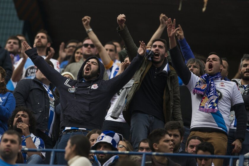Coruna's fans react during a Spanish La Liga soccer match between Atletico and Deportivo Coruna at the Vicente Calderon stadium in Madrid, Spain, Sunday, Nov. 30, 2014. Officials said a man was hospitalized in critical condition, eleven others suffered minor injuries and two were arrested after a fight broke out outside Atletico Madrid's football stadium between its fans and those of Deportivo La Coruna on Sunday. Madrid emergency service SAMUR and police said the clash between the rival fans broke out at 0800 GMT near the Vicente Calderon stadium. One man with head injuries had to be rescued from the nearby Manzanares River. The man, identified only as a 43-year-old Deportivo fan, was resuscitated and taken to Madrid's Clinico hospital. (AP Photo/Andres Kudacki)