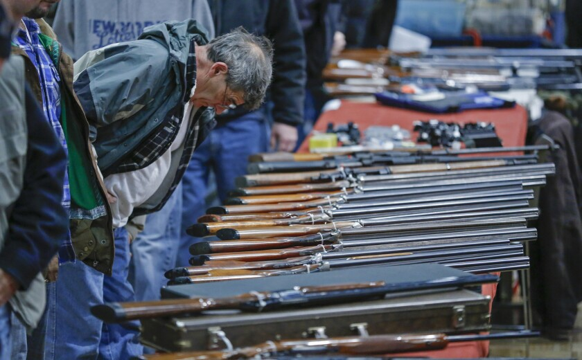 A customer looks over shotguns on display at the New York State Arms Collectors Assn. Gun Show in Albany.