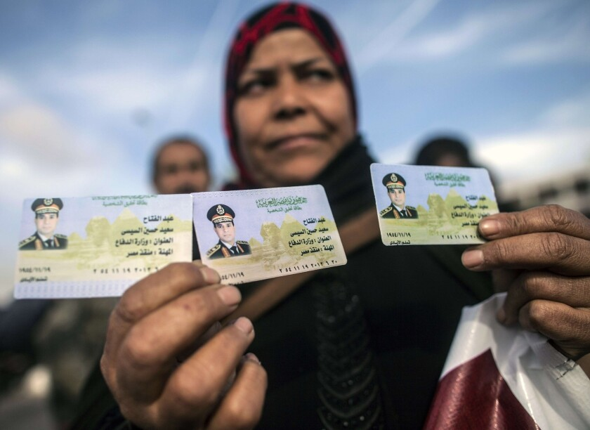 An Egyptian woman shows replica IDs with a portrait of Egypt's military commander Abdel Fattah Sisi.