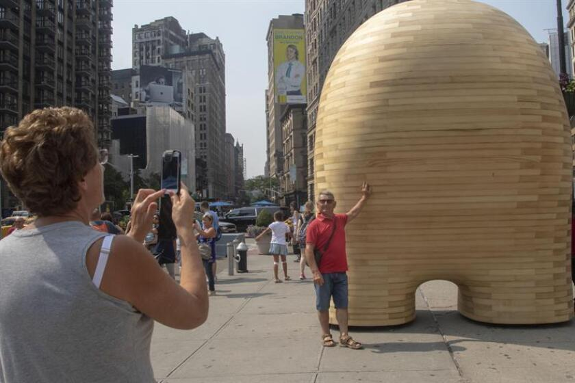 """Grupos de personas observan la escultura """"Link"""" del artista español Jorge Palacios hoy, jueves 16 de agosto de 2018, ubicada frente al emblemático edificio de Flatiron Square, en Nueva York (EE.UU.). EFE"""