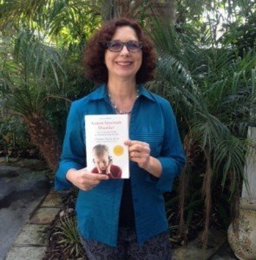 """Chantal Sicile-Kira holding her book, """"Autism Spectrum Disorder: The Complete Guide to Understanding Autism."""" Courtesy photo"""