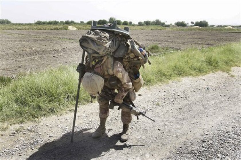 U.S. Marine Cpl. Brian Knight, of Cincinnati, Ohio, with the 2nd Marine Expeditionary Brigade, 1st Battalion 5th Marines, pauses briefly in the heat to rest with his heavy pack filled with mortar equipment, ammunition, food, and water in the Nawa district in Afghanistan's Helmand province Saturday, July 4, 2009. Taliban militants attacked a U.S. coalition base in eastern Afghanistan on Saturday with an explosives-laden truck that blew up outside the gates, sparking a two-hour gunbattle and killing two American troops, officials said.(AP Photo/David Guttenfelder)