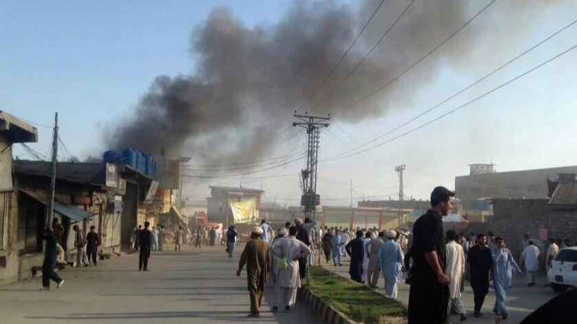 epa06045843 Smoke billows from the scene of a suicide bomb blast at Toori market in Parachinar, Paki