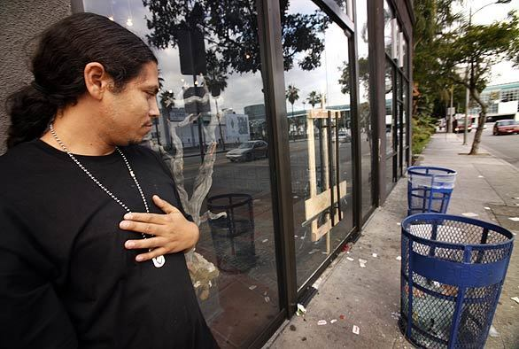 Richard Torres, owner of the Holy Grail shoe store, stands in front of his boarded-up shop. Torres' store was emptied of its stock by looters during the rioting that followed Sunday night's Lakers victory.