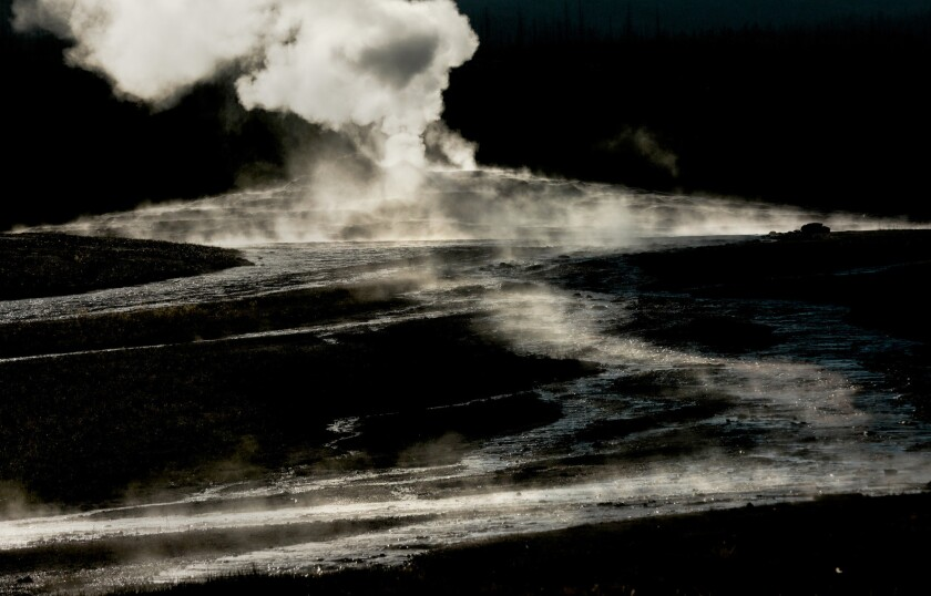 Steam rises from the base of the Old Faithful geyser in Yellowstone National Park.