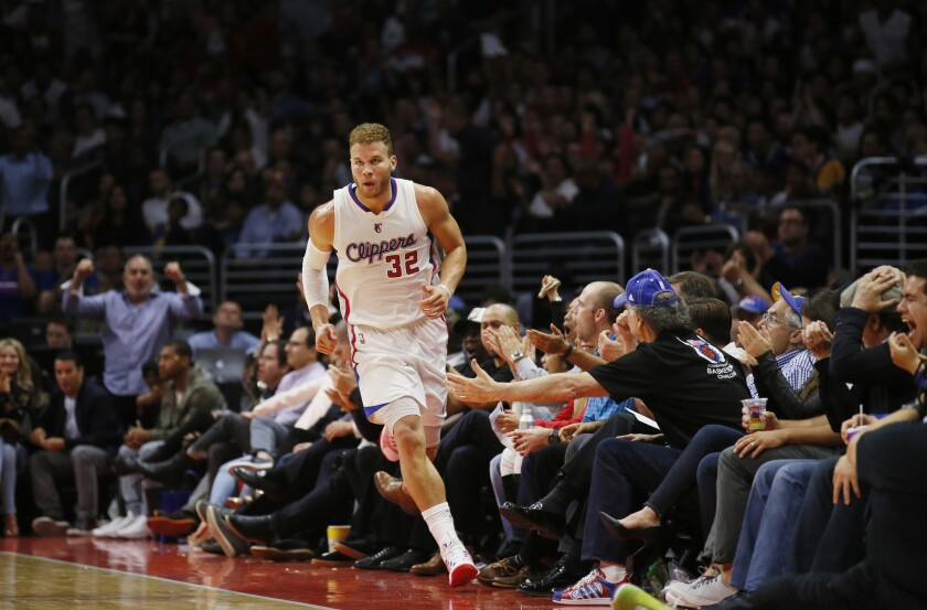 Clippers fans sitting courtside at Staples Center try to give All-Star forward Blake Griffin five after he scored against the Warriors in the second half of their game Tuesday night.
