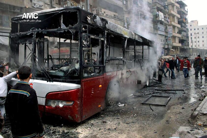 This citizen journalism image provided by Aleppo Media Center AMC which has been authenticated based on its contents and other AP reporting, shows Syrians inspecting a burnt bus after a missile fired by Syrian government aircraft hit the vehicle in the rebel-held neighborhood of al-Bab in Aleppo, S