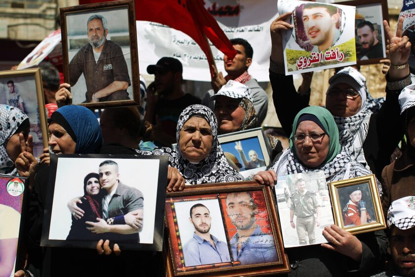Palestinian family members in the West bank town of Ramallah hold pictures of their relatives jailed in Israeli prisons as they mark Palestinian Prisoner Day.