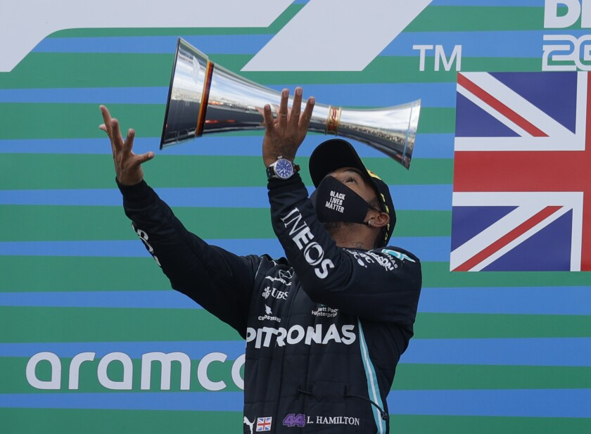 Lewis Hamilton throws the trophy in the air at the podium.