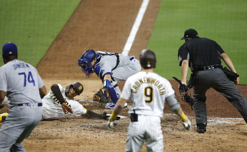Padres' Trent Grisham is tagged out by Dodgers catcher Will Smith to end the game Wednesday at Petco Park.